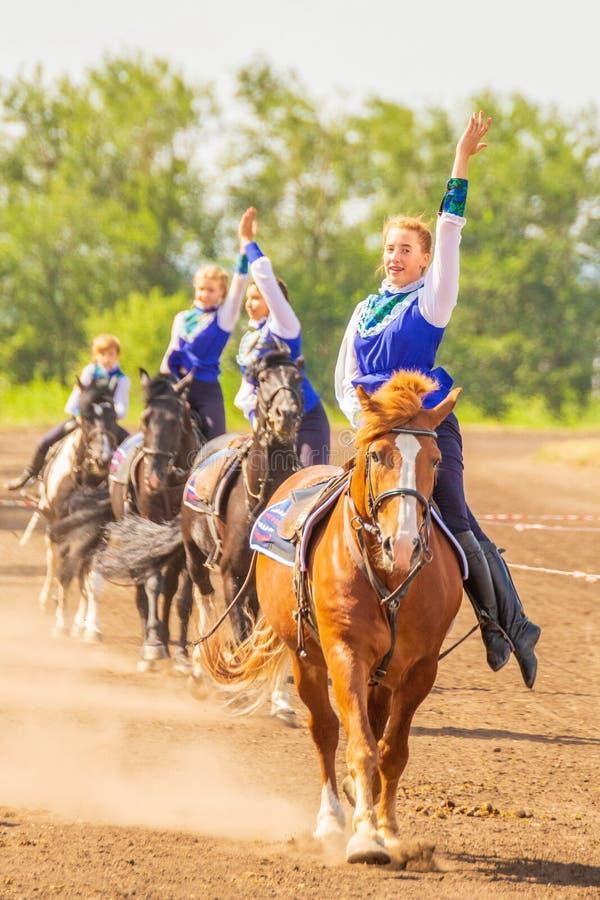 Dziewczyny od grupy dzhigitovki wykonują powikłane sztuczki na horseback obraz stock