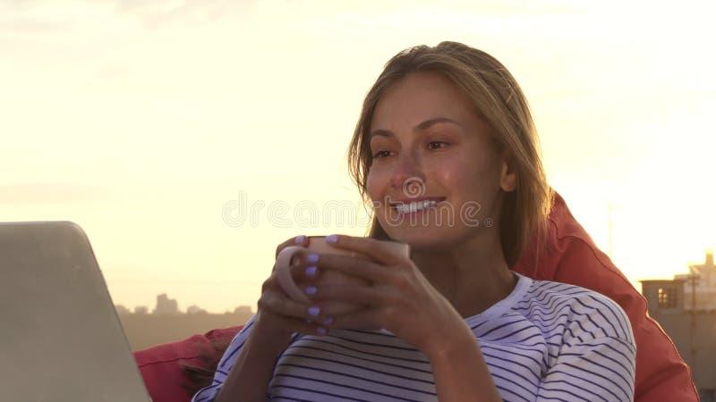 Dziewczyny odpoczynkowi napoje grżą herbaty i spojrzeń przy laptopu obsiadaniem na dachu zdjęcie royalty free