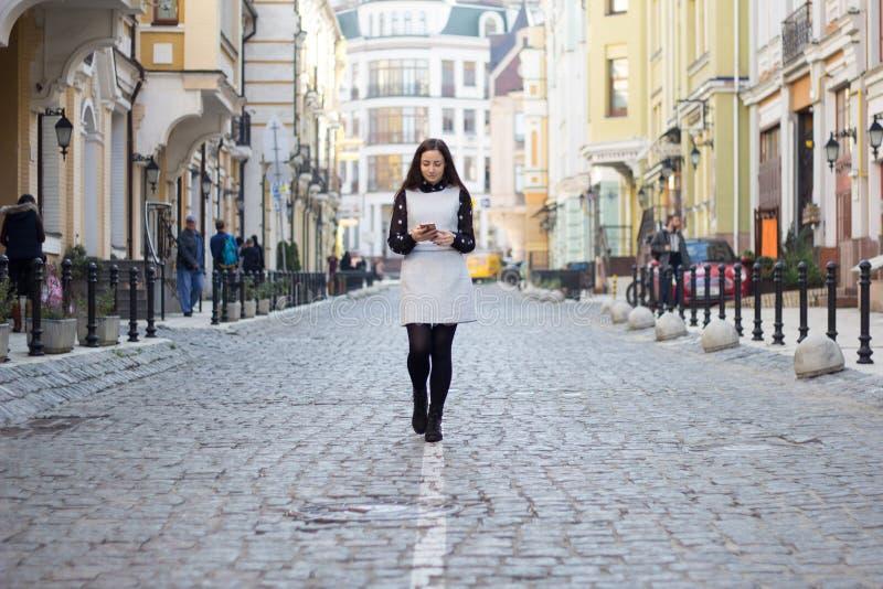 Dziewczyny odprowadzenia puszek ulica z jej telefonem fotografia stock