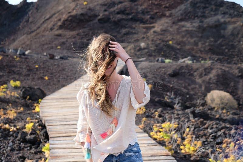 Dziewczyny odprowadzenie na wietrznej drewnianej ścieżce z włosy na jej twarzy zdjęcie stock
