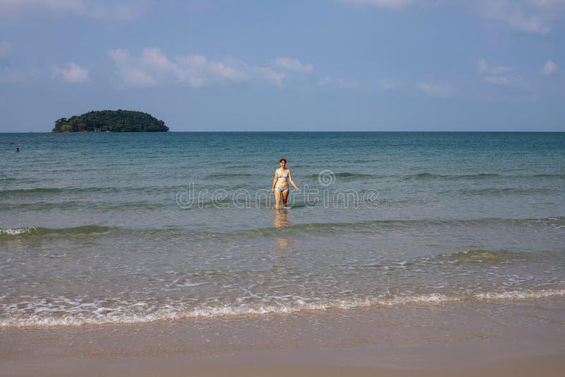 Dziewczyny odprowadzenie z wody morskiej na białej piasek plaży Tropikalny seashore widok z osamotnionym turysta podeszwy podróżn zdjęcia royalty free