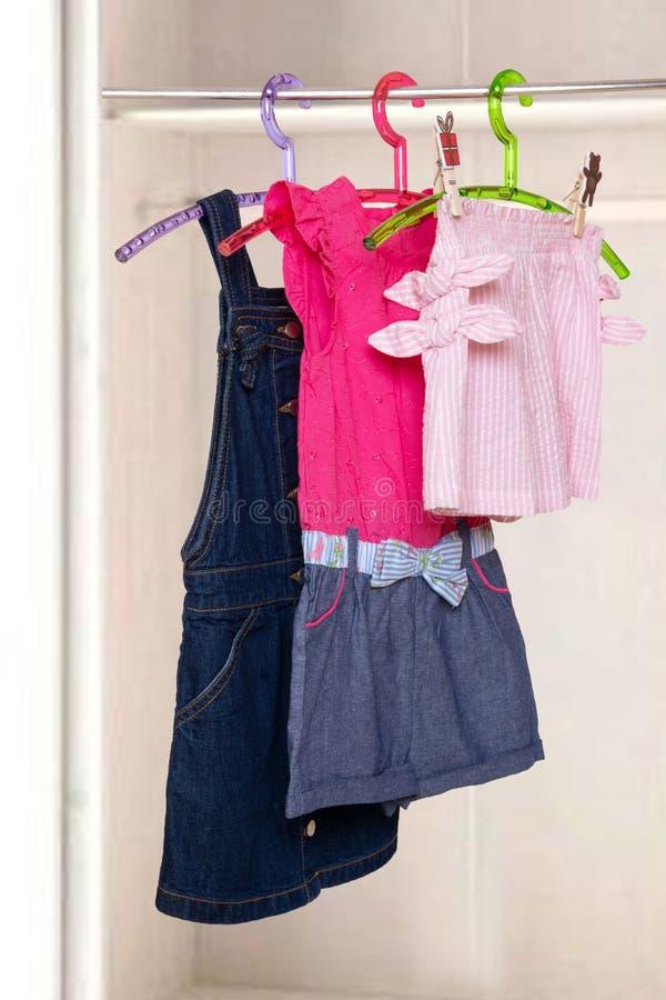 Dziewczyny odziewają na stojaku Kolaż kolorowe eleganckie lato suknie i krótcy spodnia dla małej dziewczynki na stojaku w zamazan zdjęcie royalty free