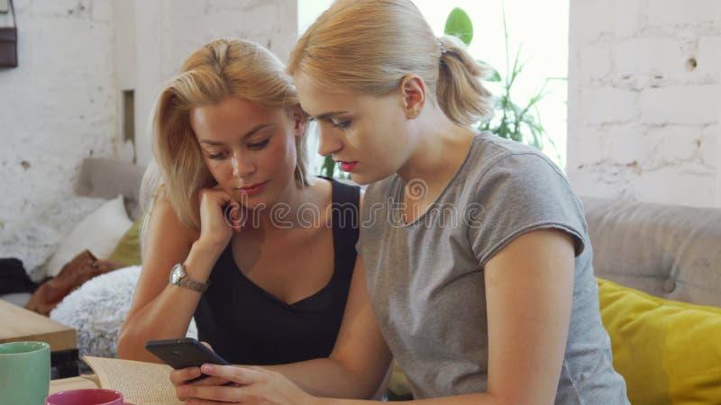 Dziewczyny oglądają coś w telefonie obraz stock