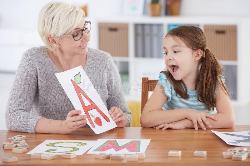 Dziewczyny pisowni listy z terapeuta fotografia stock
