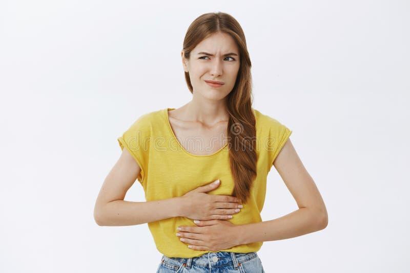 Dziewczyny pożałowanie je karmowego pobliskiego metro Portret nieradej zmartwionej kobiety czuciowa niewygoda w żołądka mienia rę zdjęcie stock