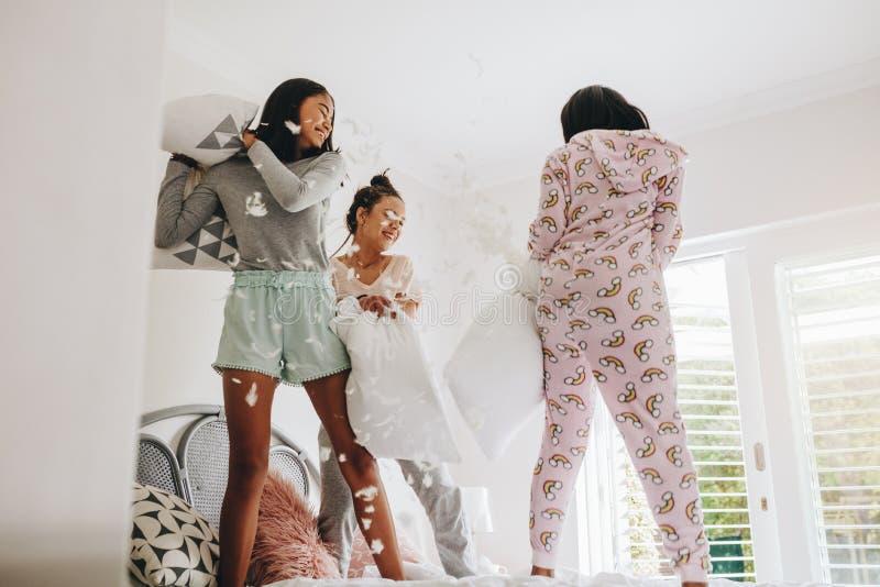 Dziewczyny poduszki walcząca pozycja na łóżku obraz stock
