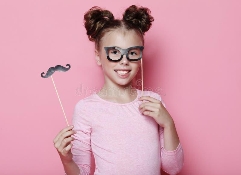Dziewczyny poza z fotografii budka podpiera szkła i wąsy Dziecko dziewczyna z partyjnymi szkłami nad różowym tłem zdjęcie royalty free