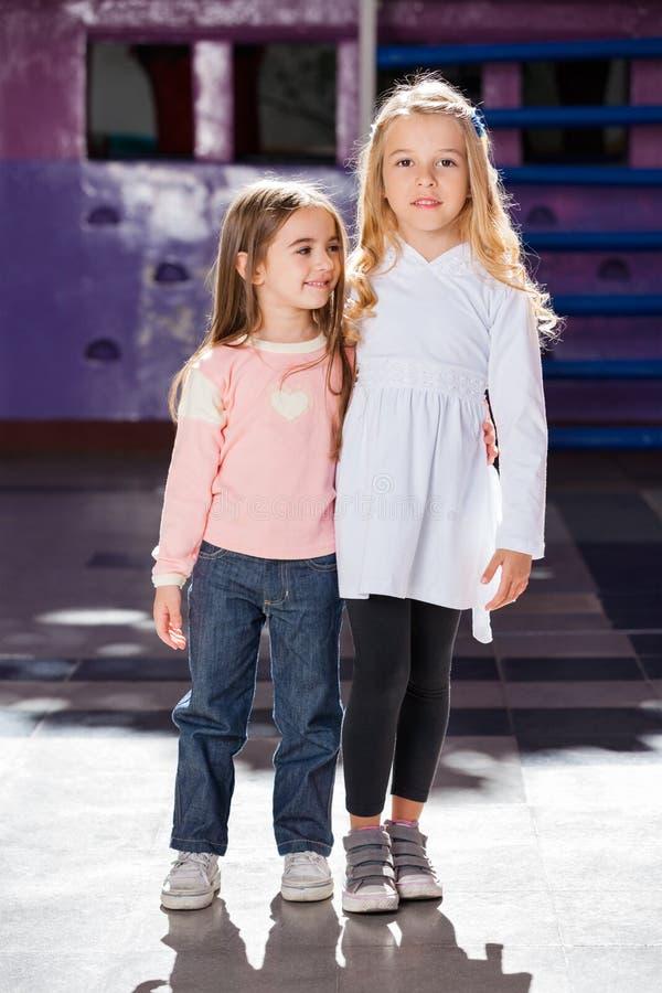 Dziewczyny pozyci ręki Wokoło Z Żeńskim przyjacielem Wewnątrz fotografia stock