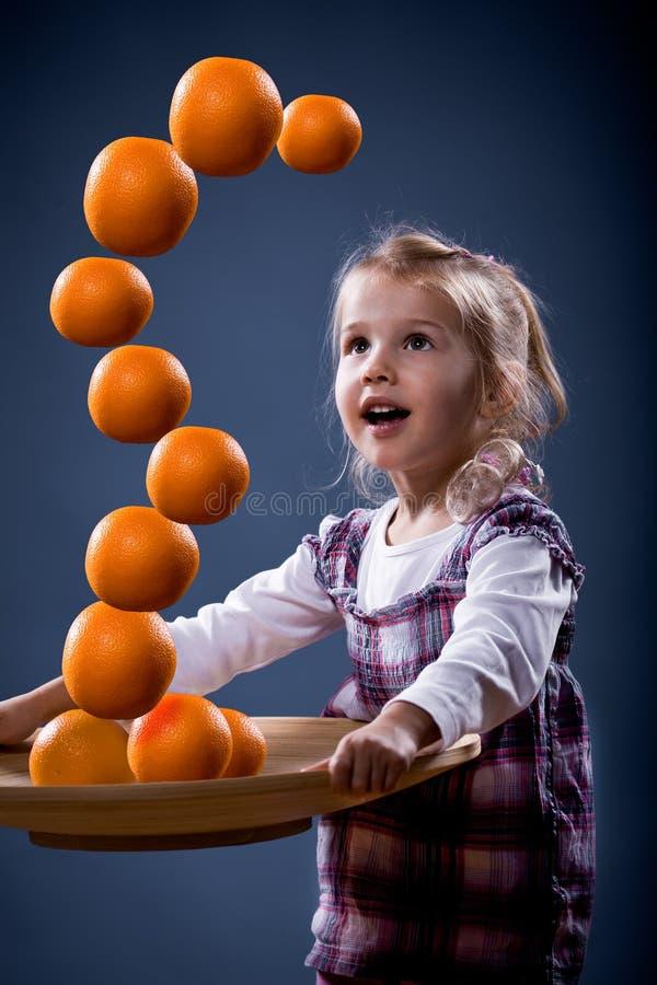 Dziewczyny równoważenia pomarańcze obrazy royalty free