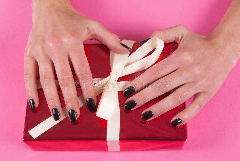 Dziewczyny ręka na czerwonym prezenta pudełku z białym łękiem odizolowywającym na różowym tle fotografia royalty free