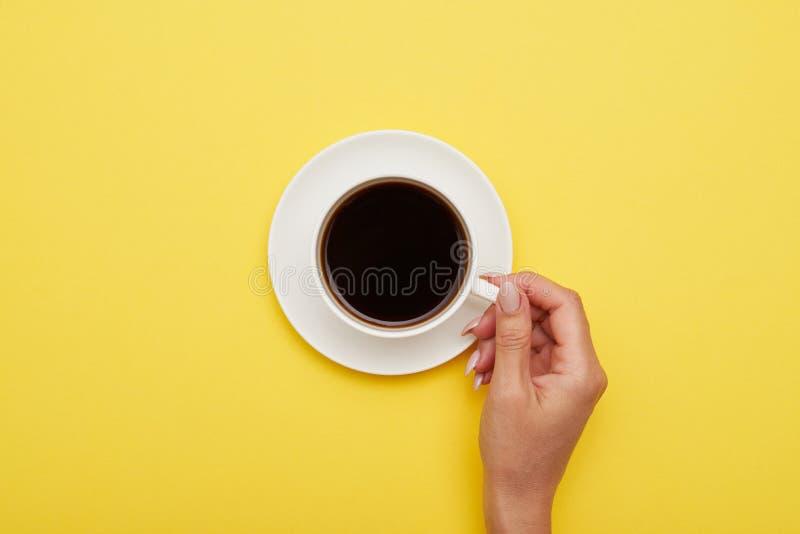 Dziewczyny ręka trzyma filiżankę smakowita kawa espresso, mieszkanie nieatutowy obrazy royalty free
