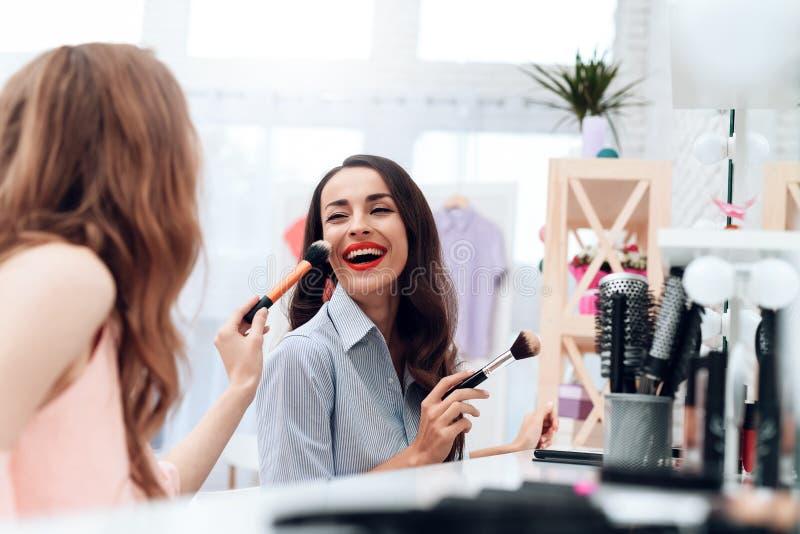Dziewczyny robią makeup w sala wystawowej Dwa pięknej dziewczyny zabawę i one uśmiechają się zdjęcie royalty free