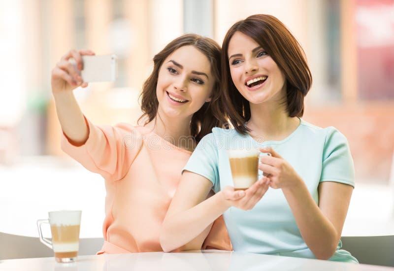 Dziewczyny robi selfie w kawiarni obrazy stock