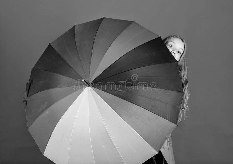 Dziewczyny rozochocona kryjówka za parasolem Kolorowy parasolowy akcesorium Prognozy pogody pojęcie Wantowy pozytyw chociaż dżdży obraz stock