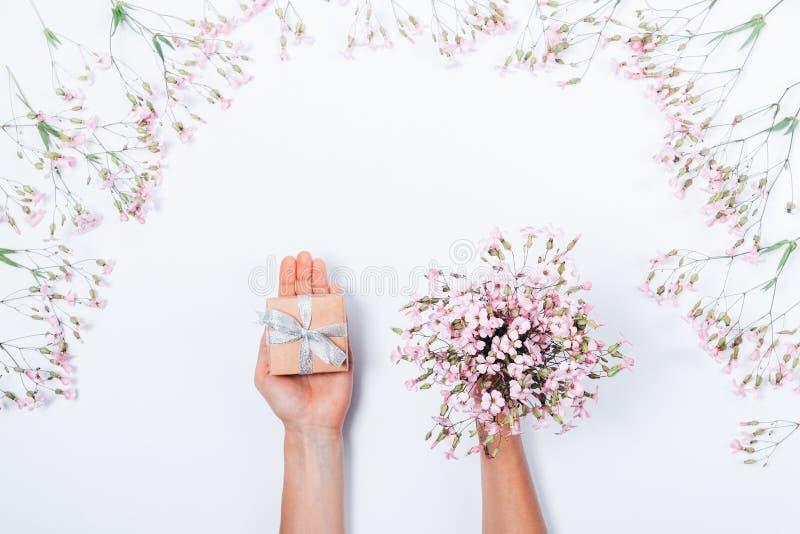 Dziewczyny ` s ręki trzyma małego prezenta pudełko z srebnym łękiem zdjęcie stock