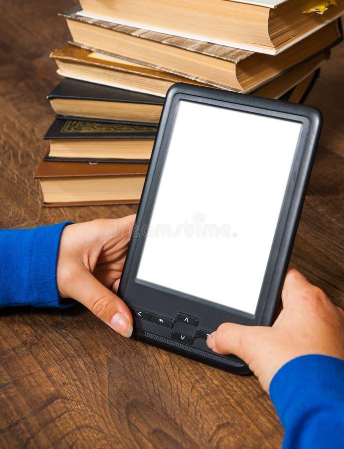 Dziewczyny ` s ręki trzymają EBook na urządzenie przenośne above stosie stara papierowa książka z pustym bielu ekranem na drewnia fotografia stock
