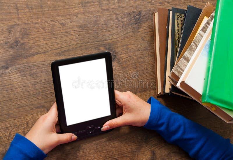 Dziewczyny ` s ręki trzymają EBook na urządzenie przenośne above stosie stara papierowa książka z pustym bielu ekranem na drewnia obraz royalty free