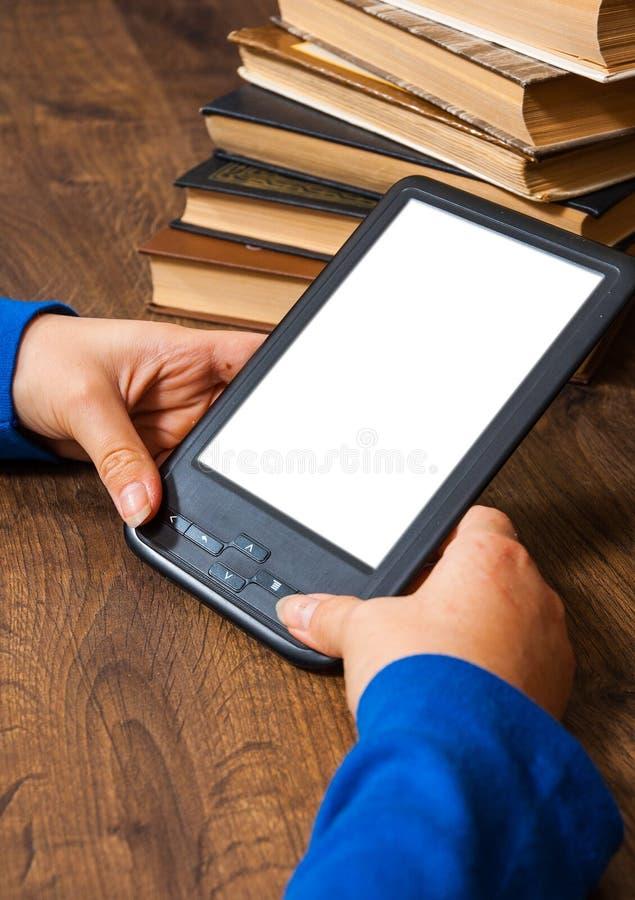 Dziewczyny ` s ręki trzymają EBook na urządzenie przenośne above stosie stara papierowa książka z pustym bielu ekranem na drewnia obrazy stock