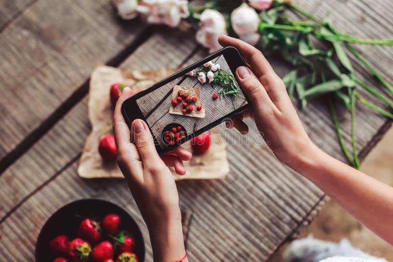 Dziewczyny ` s wręcza brać fotografię śniadanie z truskawkami smartphone Zdrowy śniadanie, fotografia royalty free