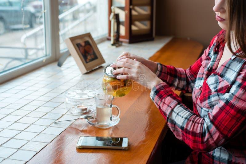 Dziewczyny sekretarka w koszula, żeńskie ręki w kawiarni okno nalewa herbaty w kubek od czajniczek kelnerki na a, obraz royalty free