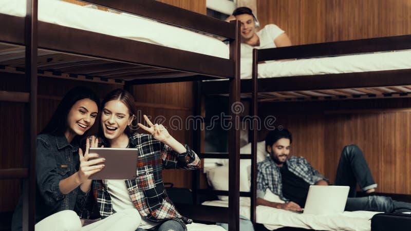 Dziewczyny siedzą na łóżku i opowiadać na wideo przy pastylką zdjęcie royalty free