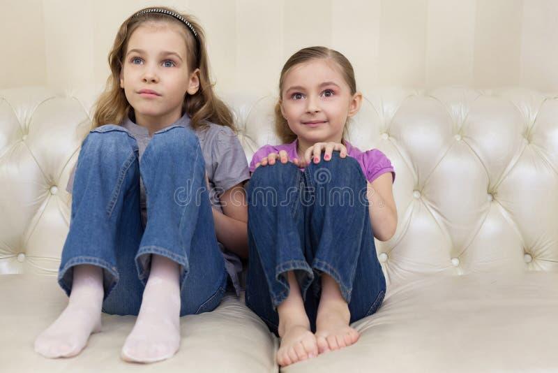 Dziewczyny siedzi na kanapie i ogląda TV zdjęcie royalty free