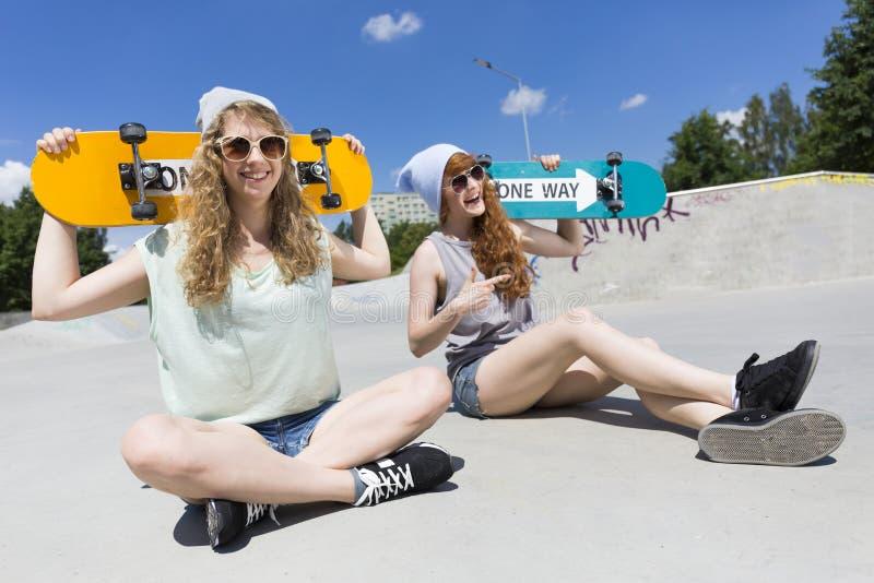 Dziewczyny siedzi z ich jeździć na deskorolce obrazy royalty free