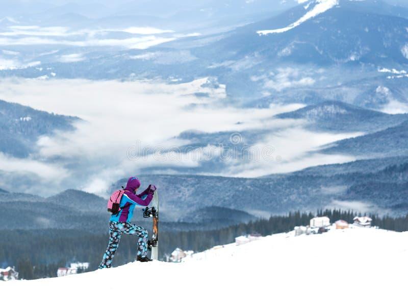Dziewczyny snowboarder pozycja na zbocze wysokiej górze obraz stock