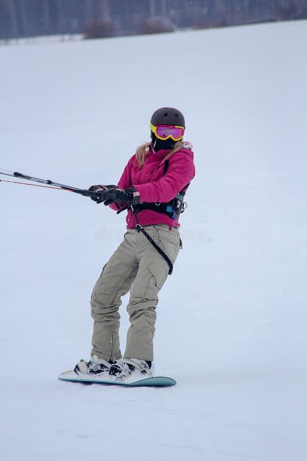 Dziewczyny Snowboarder przejażdżki Z kanią Snowkiting w zimie zdjęcie royalty free