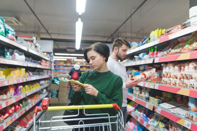Dziewczyny spojrzenia przy jej smartphone i jej mąż czytają produkt etykietkę podczas gdy robiący zakupy, obraz stock