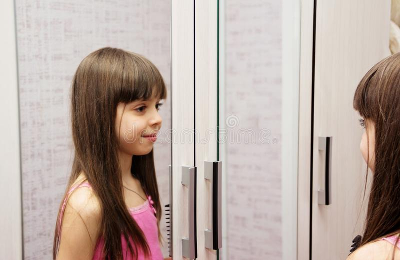 Dziewczyny spojrzenia przy ona w lustrze zdjęcie royalty free