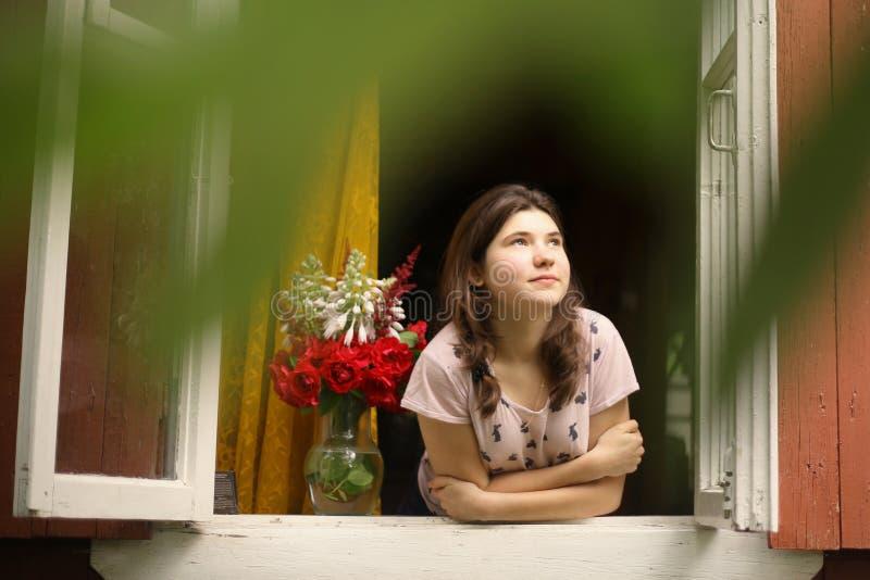 Dziewczyny spojrzenie z okno przy rankiem od chałupy lata domu obraz stock