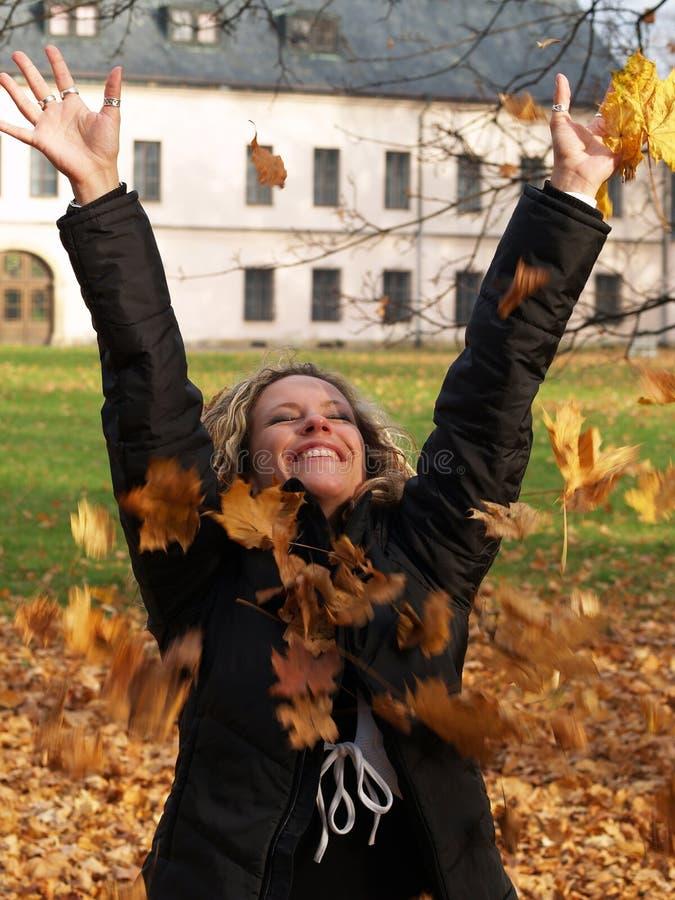 dziewczyny szczęśliwych liść klonowy miotanie zdjęcia stock