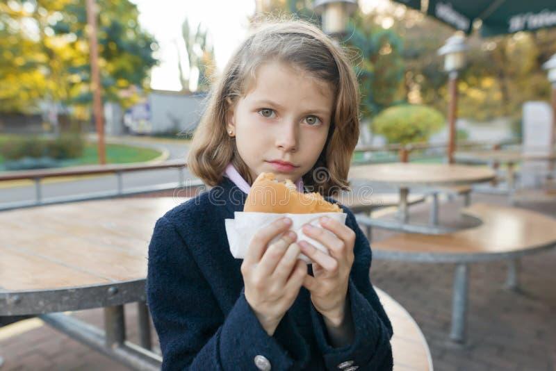 Dziewczyny szkoły podstawowej uczeń je hamburger, kanapka przy plenerową kawiarnią obraz royalty free