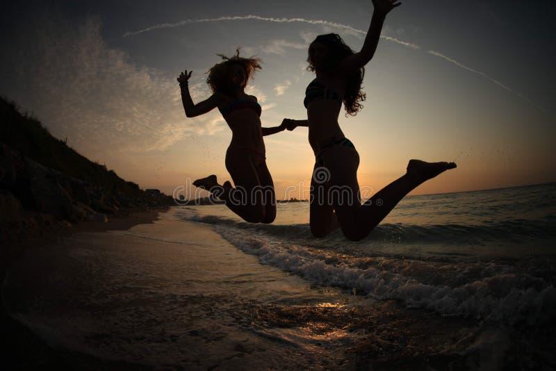 Dziewczyny TANCZY W zmierzchu NA morzu zdjęcia royalty free