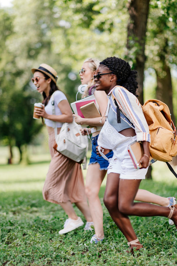 Dziewczyny trzyma książki i bieg w parku w okularach przeciwsłonecznych obraz royalty free