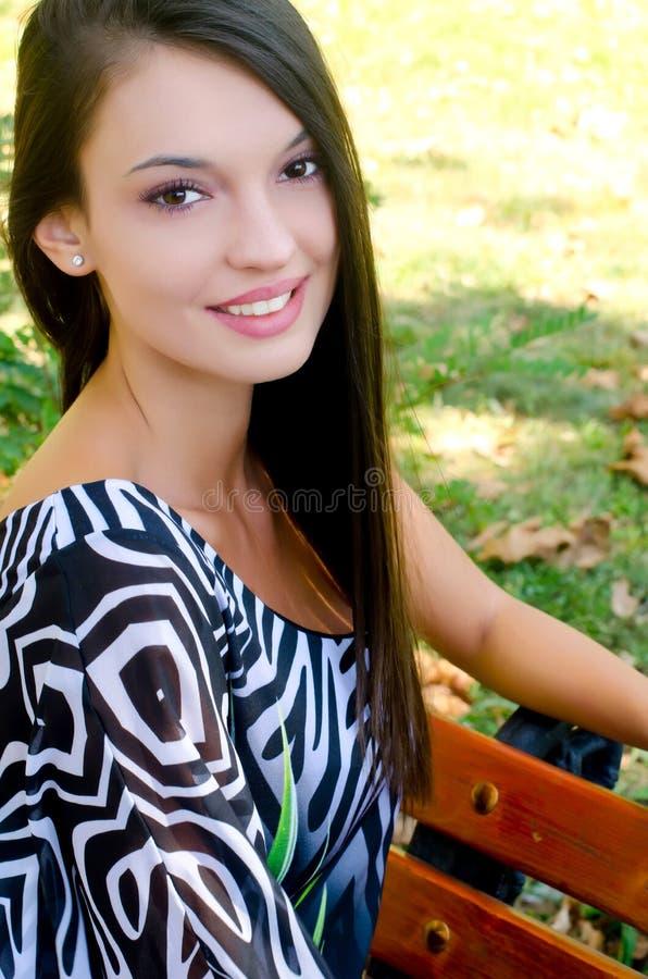 Dziewczyny uśmiechnięty obsiadanie na ławce w parku. zdjęcia royalty free