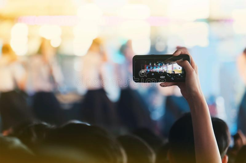 Dziewczyny używają smartphones brać obrazek przy koncertami obrazy royalty free