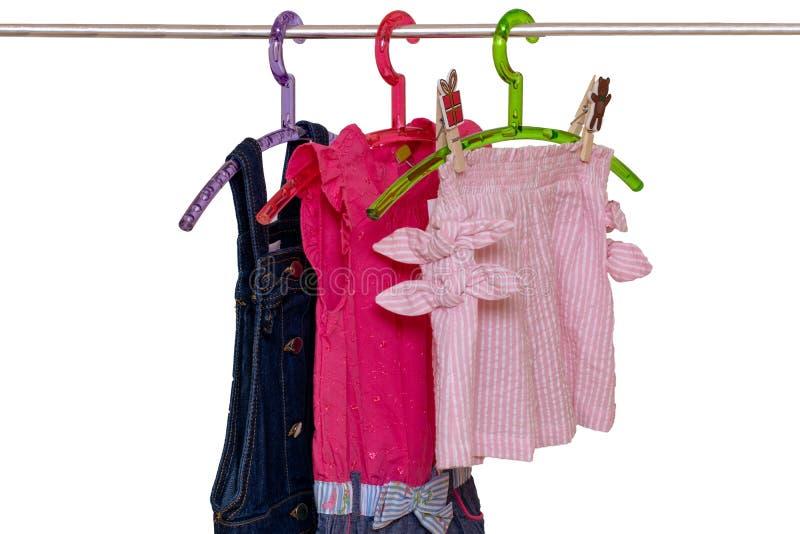 Dziewczyny ubrania na stojaku Zbliżenie kolorowych, stylowych sukienek letnich i krótkich spodni dla dziewczynki na szafie wyizol obrazy royalty free