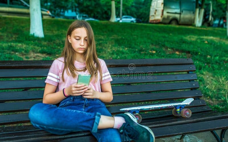 Dziewczyny uczennicy 12-15 lat, siedzi ławki lata miasto, łyżwa W ręki smartphone, online zastosowanie, socjalny zdjęcia royalty free