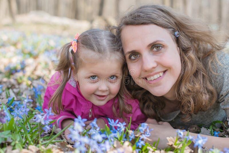 Dziewczyny wąchają kwiaty podczas gdy siedzący na zielonej łące obrazy stock