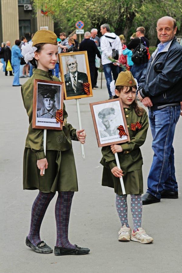 Dziewczyny w wojskowego uniformu chwyta portretach ich krewni w akci ` pułku Nieśmiertelnym ` na zwycięstwo dniu w Volgograd zdjęcie royalty free