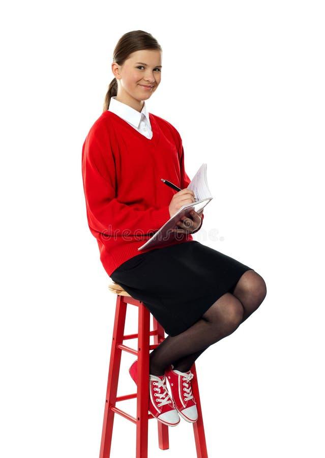 dziewczyny wysoki notatnika obsiadania stolec writing obrazy stock