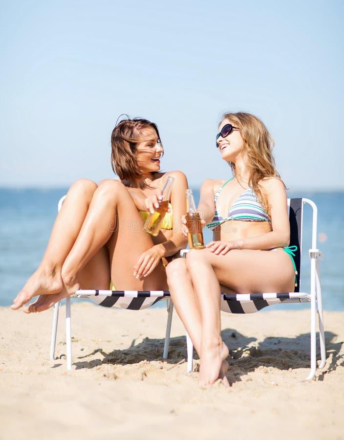 Dziewczyny z napojami na plażowych krzesłach obraz stock