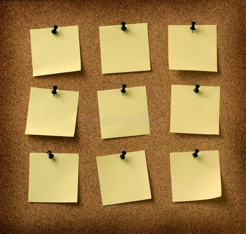 Dziewięć żółtych notatek przyczepiających grunge korka tło obrazy stock