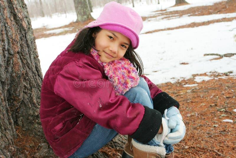 Dziewięć roczniaka dziewczyna siedzi outdoors w zimie zdjęcie stock