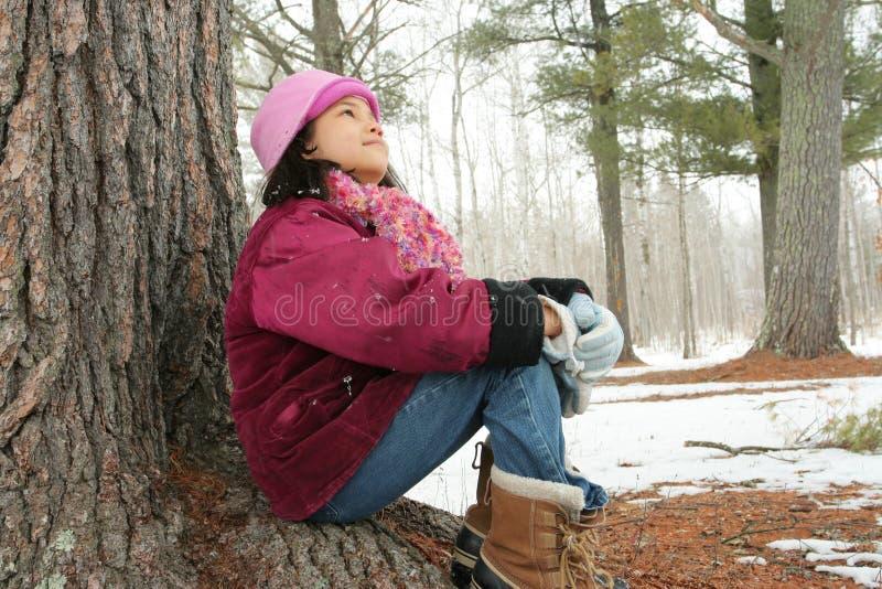 Dziewięć roczniaka dziewczyna siedzi outdoors w zimie obraz stock
