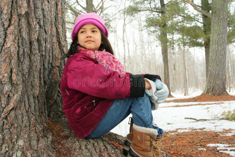 Dziewięć roczniaka dziewczyna siedzi outdoors w zimie zdjęcia stock