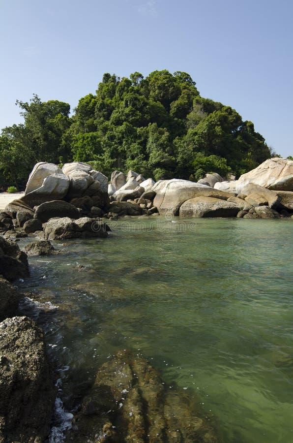 Dzika tropikalna wyspa i skalisty denny brzeg pod jaskrawym słonecznym dniem i niebieskim niebem obraz stock