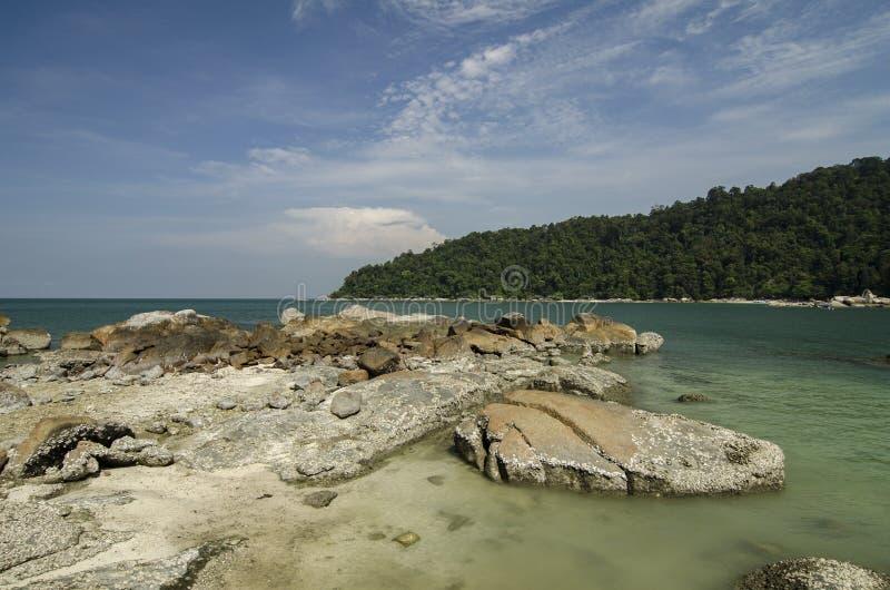 Dzika tropikalna wyspa i skalisty denny brzeg pod jaskrawym słonecznym dniem i niebieskim niebem obrazy stock